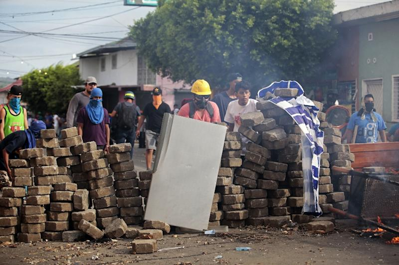 Demonstrators protect themselves behind barricades last month in the Nicaraguan town of Masaya (AFP Photo/DIANA ULLOA)