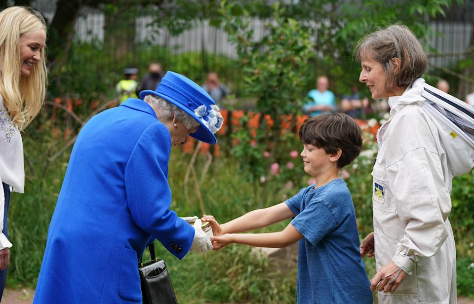 Britain's Queen Elizabeth II is given a jar of honey during a visit to The Childrens Wood Project in Glasgow on June 30, 2021, as part of her traditional trip to Scotland for Holyrood Week. (Photo by Andrew Milligan / POOL / AFP) (Photo by ANDREW MILLIGAN/POOL/AFP via Getty Images)
