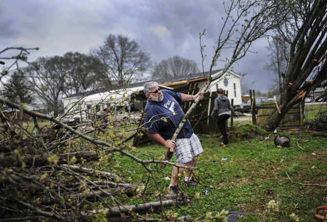 <p>Mark Tenney helps in the cleanup of his neighbor Bob Walters' house, Tuesday, March 20, 2018, in Ardmore, Ala., after a violent storm went swept through the area the night before. (Photo: Jeronimo Nisa/The Decatur Daily via AP) </p>