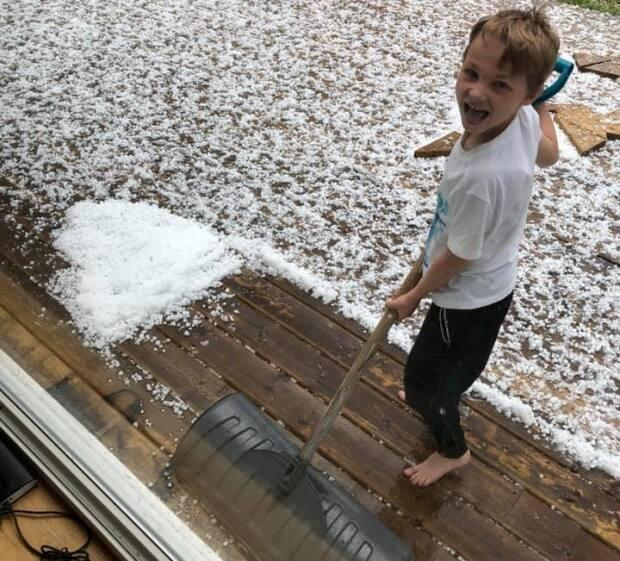 Six-year-old Kayden Getson dug out a snow shovel to deal with the hail that fell in Baker Settlement in Lunenburg County on Tuesday evening.