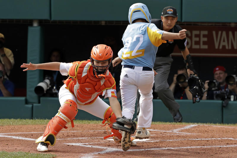 River Ridge, Louisiana, catcher Egan Prather, left, catches the leg of Wailuku, Hawaii's Bransyn Hong (22) for the out at home in the first inning of the United State Championship baseball game at the Little League World Series tournament in South Williamsport, Pa., Saturday, Aug. 24, 2019. (AP Photo/Gene J. Puskar)