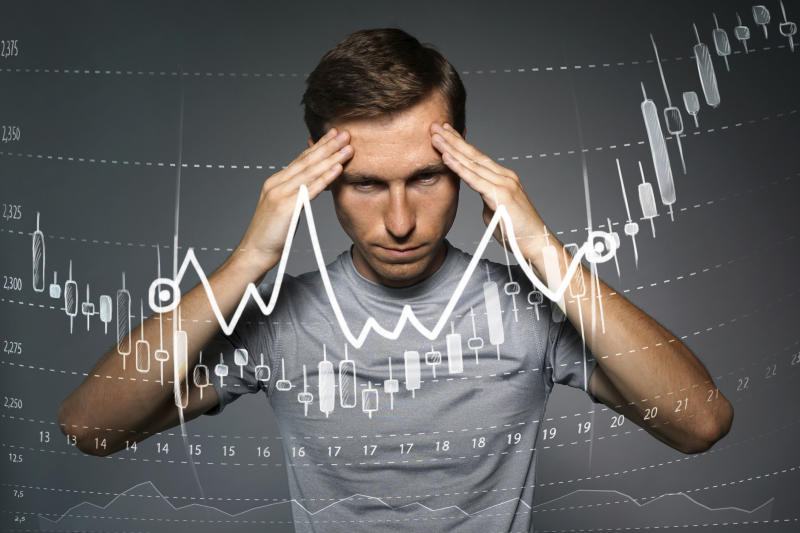 Man with hands held up to the side of his head and a stock chart in the foreground trending upward