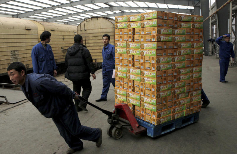 "In this Friday, Feb. 24, 2006 photo, a worker loads boxes of foods at a freight station at the Shuanghui Group in Luohe city in central China's Henan province. The force behind China's biggest takeover of an American company is a 71-year-old meat-packing entrepreneur dubbed ""China's Chief Butcher"" by the press who built an empire on his country's voracious appetite for pork. The $4.7 billion bid for Smithfield Foods by Wan Long, chairman of Shuanghui International, is another big step up for Chinese entrepreneurs who are emerging from the shadow of state-owned corporate giants and expanding on the global stage. (AP Photo) CHINA OUT"