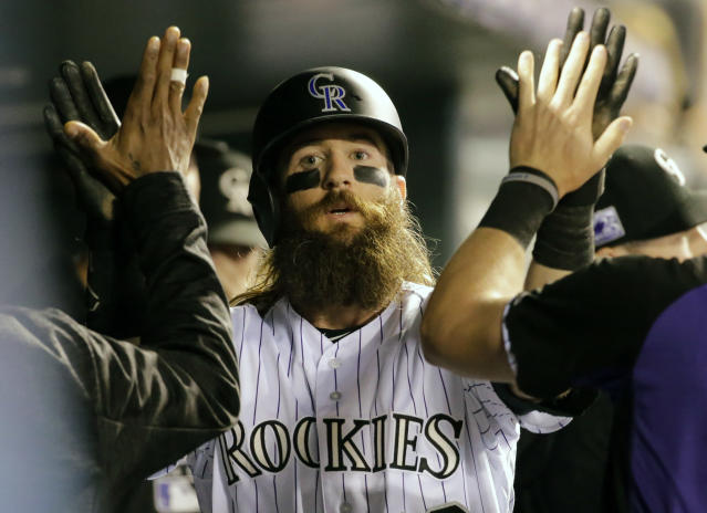 Colorado Rockies' Charlie Blackmon is congratulated by teammates in the dugout after scoring a run against the Philadelphia Phillies during the third inning of a baseball game on Monday, Sept. 24, 2018, in Denver. (AP PhotoJack Dempsey)