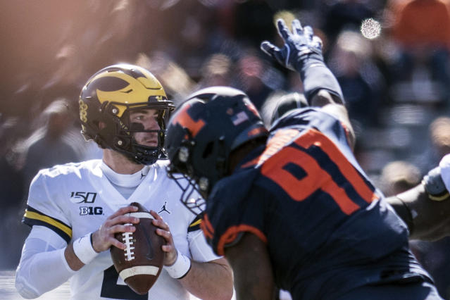 Michigan quarterback Shea Patterson (2) keeps his eye on a receiver as he is pressured by Illinois' Bobby Roundtree (97) in the second half of an NCAA college football game between Illinois and Michigan, Saturday, Oct. 12, 2019, in Champaign, Ill. (AP Photo/Holly Hart)
