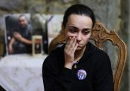 Karlin, wife of firefighter Charbel Karam and sister of firefighter Najib Hitti, looks on, during an interview with Reuters in Qartaba