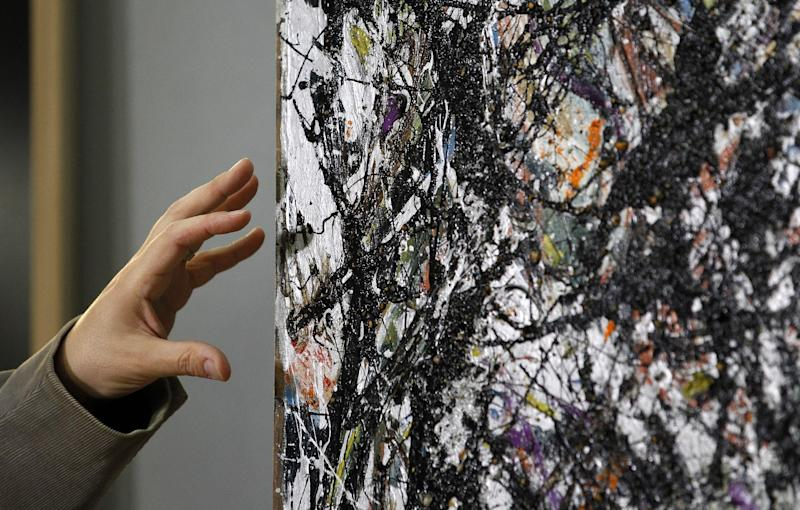 Nicholas Dorman, chief conservator for the Seattle Art Museum, points to the canvas as he talks about his on-going restoration work of Jackson Pollock's painting Sea Change during a news conference Tuesday, Nov. 27, 2012, at the museum in Seattle. The celebrated piece, part of SAM's permanent collection, was painted in 1947 and altered in 1970 with a coat of varnish. Dorman is several months into the restoration work, which is complicated by the uneven surface and multiple layers of media, including several types of paint and imbedded gravel. The restoration is sponsored by Bank of America's Art Conservation Project, which enabled SAM staff and consulting experts to undertake a study of the original materials and evaluate the impact of materials used in conservation treatments. (AP Photo/Elaine Thompson)