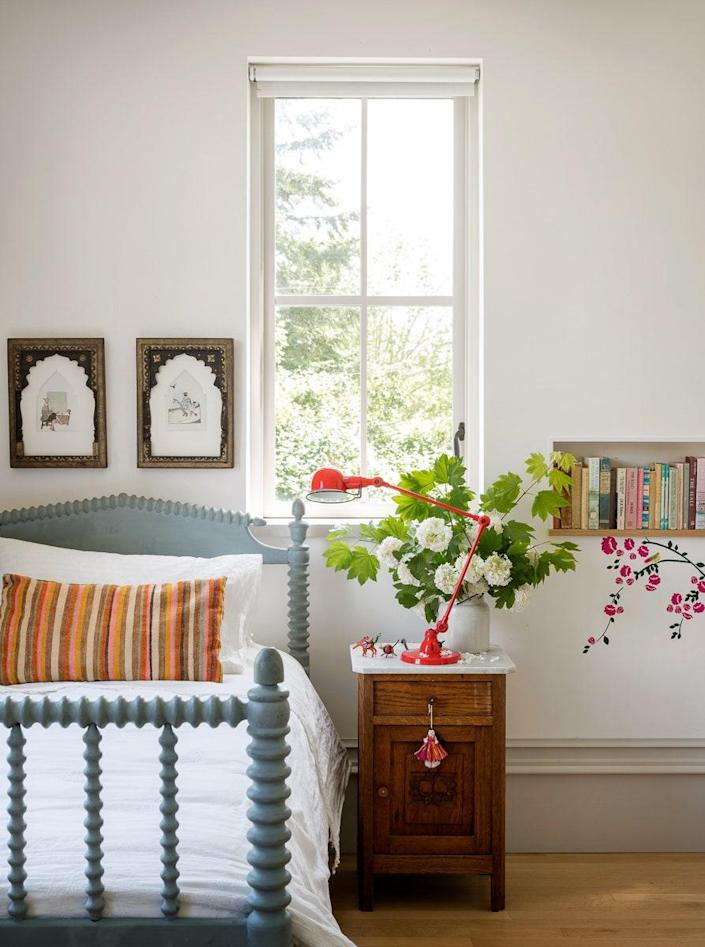 In Penelope's bedroom; the milk-painted vintage bed and frames were brought back from a trip to India.