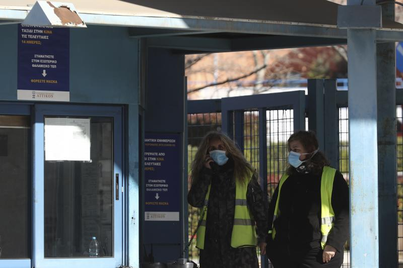 Security personnel wearing face masks stand at the gate of Attiko Hospital in Athens, Saturday, Feb. 29, 2020. Greek Health Ministry said all carnival events in Greece would be suspended as a precautionary measure. (AP Photo/Yorgos Karahalis)