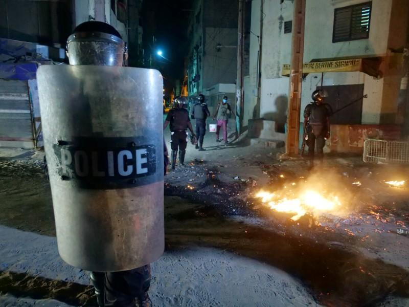 A riot police officer holds a shield while others try to put out a fire in the middle of the street during protests in Dakar