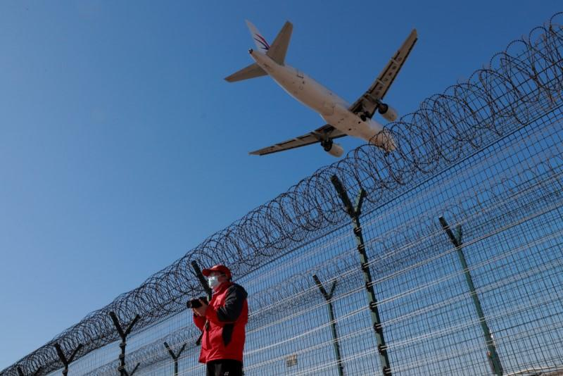 A man wearing a protective mask stands at a fence surrounding Beijing Capital International as a plane lands in Beijing as the country is hit by an outbreak of the novel coronavirus