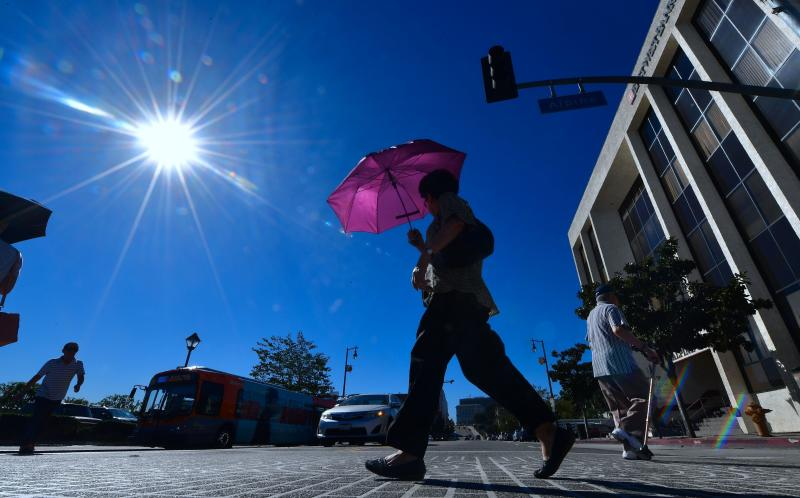 A pedestrian uses an umbrella as a heat shield in Los Angeles on Tuesday, when temperatures climbed past 100 downtown. (FREDERIC J. BROWN via Getty Images)