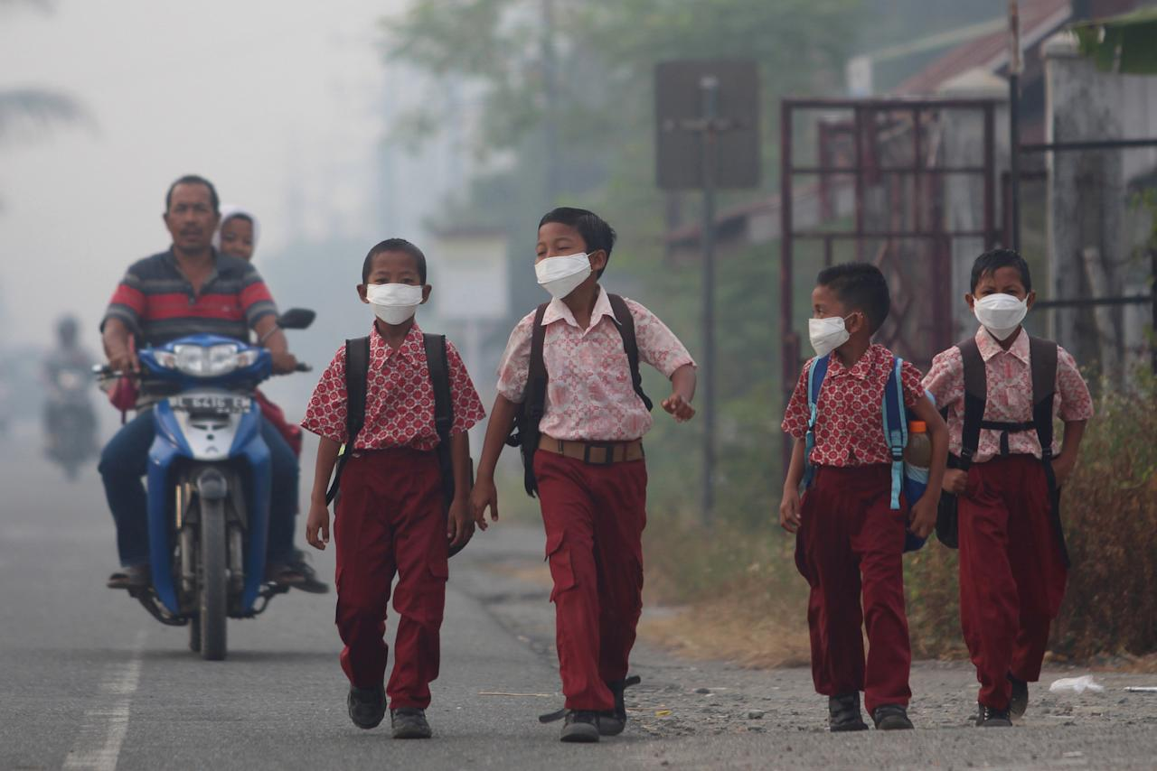 Students use masks as they walk to school at Suak Raya village in Aceh Barat, Aceh province, Indonesia July 27, 2017 in this photo taken by Antara Foto. Antara Foto/Syifa Yulinnas via REUTERS. ATTENTION EDITORS - THIS IMAGE WAS PROVIDED BY A THIRD PARTY. MANDATORY CREDIT. INDONESIA OUT. NO COMMERCIAL OR EDITORIAL SALES IN INDONESIA.