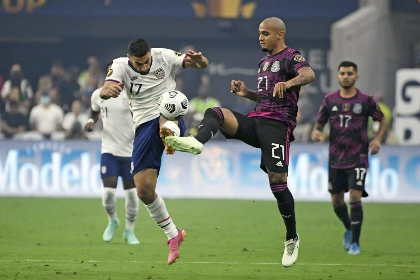 United States midfielder Sebastian Lletget (17) and Mexico defender Luis Rodriguez battle for the ball during the first half of the CONCACAF Gold Cup final soccer match, Sunday, Aug. 1, 2021, in Las Vegas. (AP Photo/David Becker)