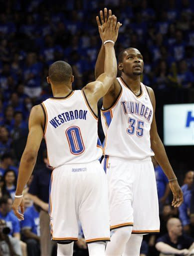 Oklahoma City Thunder guard Russell Westbrook (0) and forward Kevin Durant (35) exchange high-fives in the first quarter of Game 1 in a first-round NBA basketball playoff series in Oklahoma City, Saturday, April 28, 2012. (AP Photo/Sue Ogrocki)