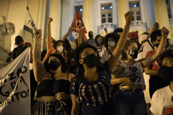 Demonstrators shout slogans during a protest against the government's response in combating COVID-19 and also asking for the extension of emergency aid by the federal government amid the pandemic in Rio de Janeiro, Brazil, Thursday, Feb. 18, 2021. (AP Photo/Silvia Izquierdo)