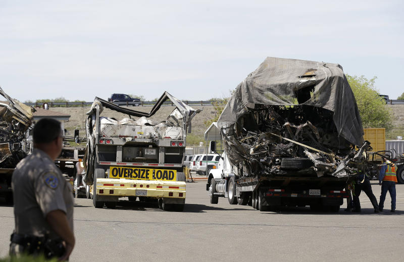 A California Highway Patrol officer stands at a gate as the demolished remains of a FedEx truck sit in a CalTrans maintenance station in Willows, Calif., Friday, April 11, 2014. At least ten people were killed and dozens injured in the fiery crash on Thursday, April 10, between a FedEx truck and a bus carrying high school students on a visit to a Northern California college. (AP Photo/Jeff Chiu)