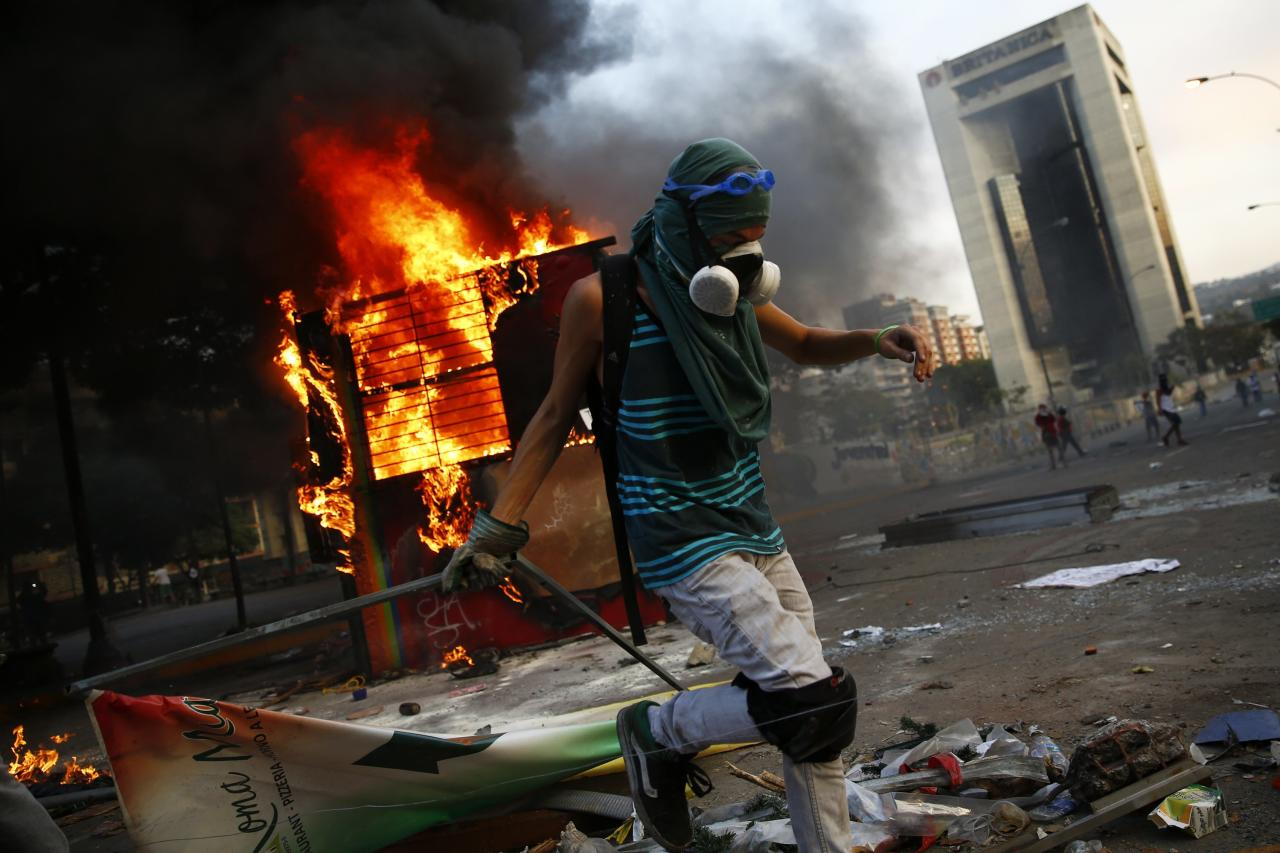An anti-government protester sets up a barricade next to a burning kiosk during a protest at Altamira square in Caracas March 9, 2014. Latin American foreign ministers will meet next week to discuss the unrest in Venezuela that has left at least 20 dead and convulsed the South American OPEC nation, diplomatic sources said on Friday. REUTERS/Jorge Silva (VENEZUELA - Tags: CIVIL UNREST POLITICS TPX IMAGES OF THE DAY)