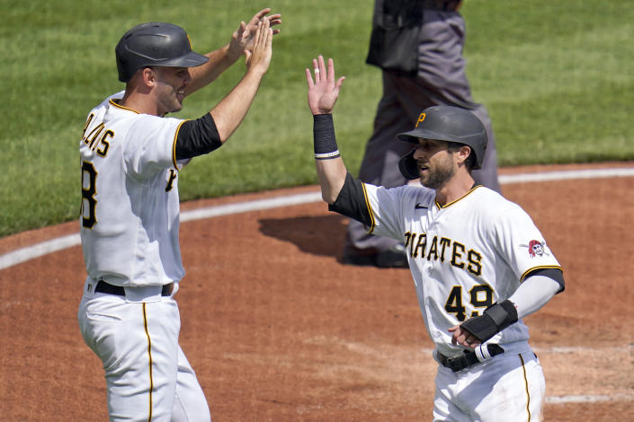 Pittsburgh Pirates' Jacob Stallings, left, and Dustin Fowler, right, celebrate after scoring on a single during the second inning of a baseball game in Pittsburgh, Sunday, April 11, 2021. (AP Photo/Gene J. Puskar)