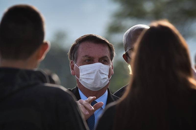 Wearing a protective face mask, Brazil's president Jair Bolsonaro arrives for the National Flag Raising ceremony and greet his supporters in front of Alvorada Palace amid the Coronavirus (COVID-19) pandemic, in Brasilia, Brazil, on Tuesday, June 9, 2020. (Photo by Andre Borges/NurPhoto via Getty Images)