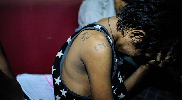 Eduardo, a 13 year old underage member of a prison gang is picked up by police during a night time drug raid in a shanty community on June 22, 2016 in Manila. Photo: Getty Images/Dondi Tawatao