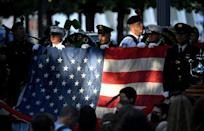 New York police and firefighters hold a US flag as a band plays the US National Anthem at the National 9/11 Memorial during a ceremony commemorating the 20th anniversary of the 9/11 attacks on the World Trade Center, in New York, on September 11, 2021 (AFP/Ed JONES)