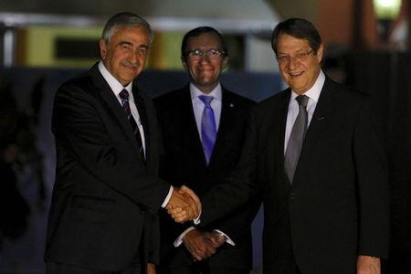 Turkish Cypriot leader Akinci shakes hands with Greek Cypriot leader and Cyprus President Anastasiades, as UN envoy Barth Eide looks on, before a meeting in Nicosia