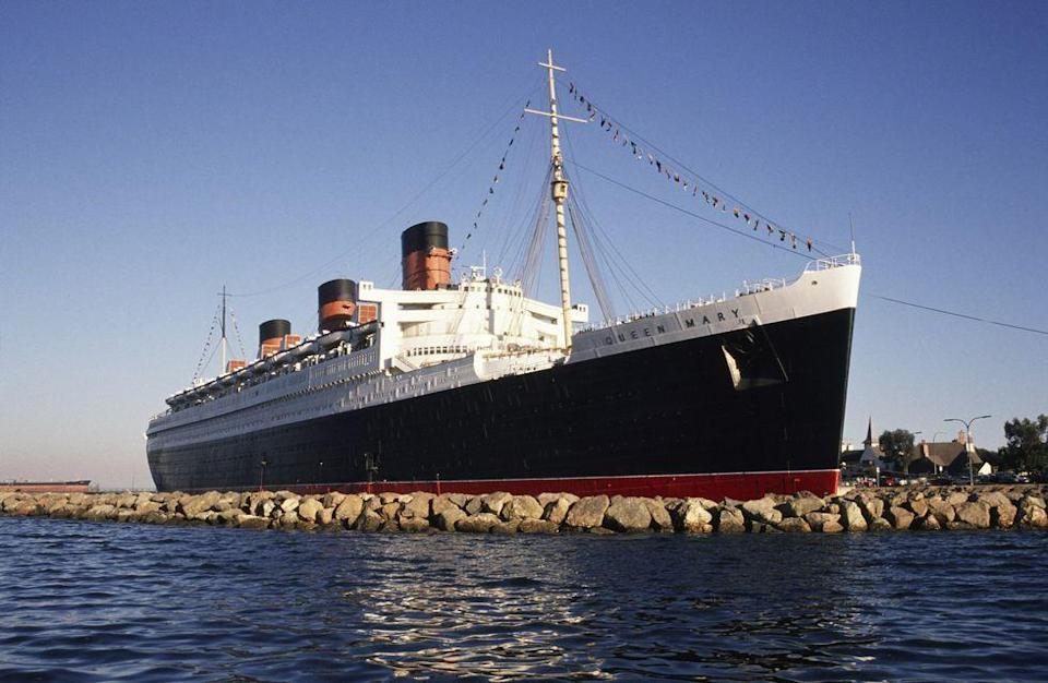 """<p>Plenty of ghost hunters have explored this ship that's now docked in Long Beach, California. They've specifically searched stateroom B340 (which, FYI, you can stay overnight in!). <a href=""""https://www.queenmary.com/hotel/rooms/b340/"""" rel=""""nofollow noopener"""" target=""""_blank"""" data-ylk=""""slk:Records of paranormal activity"""" class=""""link rapid-noclick-resp"""">Records of paranormal activity</a> in the room date back to 1967 with complaints of someone knocking on the door in the middle of the night. Other classic spooky complaints include bathroom lights turning on, faucets running, and doors shutting—all by themselves. The vessel is believed to be haunted by spirits of <a href=""""https://www.latimes.com/archives/la-xpm-1988-06-11-vw-4030-story.html"""" rel=""""nofollow noopener"""" target=""""_blank"""" data-ylk=""""slk:deceased crew and passengers"""" class=""""link rapid-noclick-resp"""">deceased crew and passengers</a> from its previous voyages.</p>"""