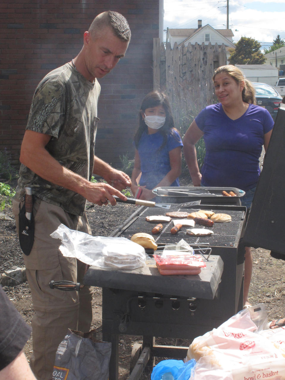A volunteer cooks hamburgers and hot dogs for storm evacuees in Manville, N.J., Friday Sept. 3, 2021. The central New Jersey town was one of the hardest hit areas as the remnants of Hurricane Ida swept through New Jersey. (AP Photo/Wayne Parry)