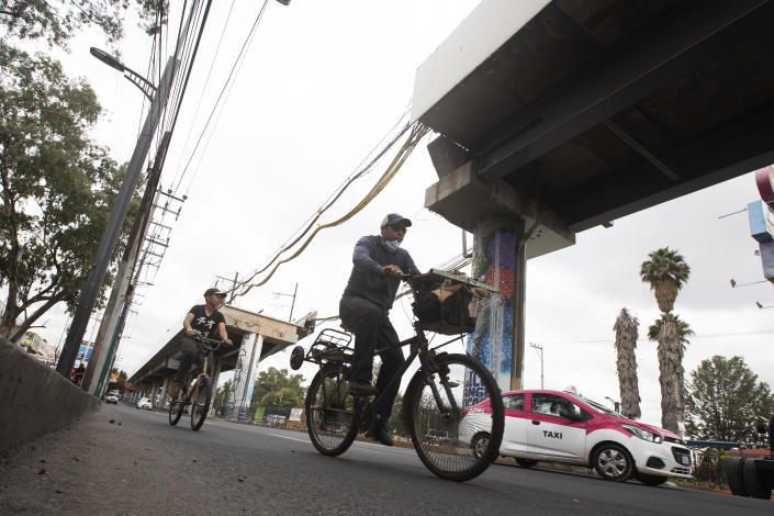 Bicyclists pedal past the site where an elevated section of the subway Line 12 collapsed in early May, in Mexico City, Thursday, June 17, 2021. A visual inspection has found problems in about one-third of the elevated Line 12, one span of which collapsed on May 3, killing 26 people. (AP Photo/Marco Ugarte)