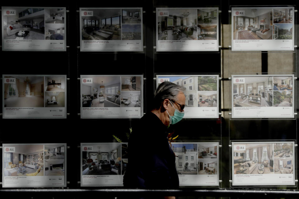 A man wearing a face mask to protect from coronavirus walks past the window of an estate agent in the Knightsbridge area of central London, Wednesday, May 20, 2020. UK House Price Index average sales figures for March 2020 released today show a 0.2% drop from February 2020 and a 2.1% increase over March last year. The coronavirus lockdown began in the UK on March 24. (AP Photo/Matt Dunham)