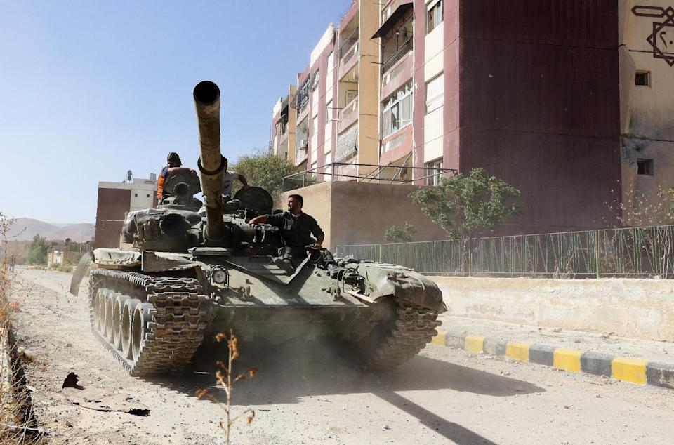 A Syrian tank drives past damaged buildings in Adra northeast of the capital Damascus, on September 25, 2014 (AFP Photo/Louai Beshara)
