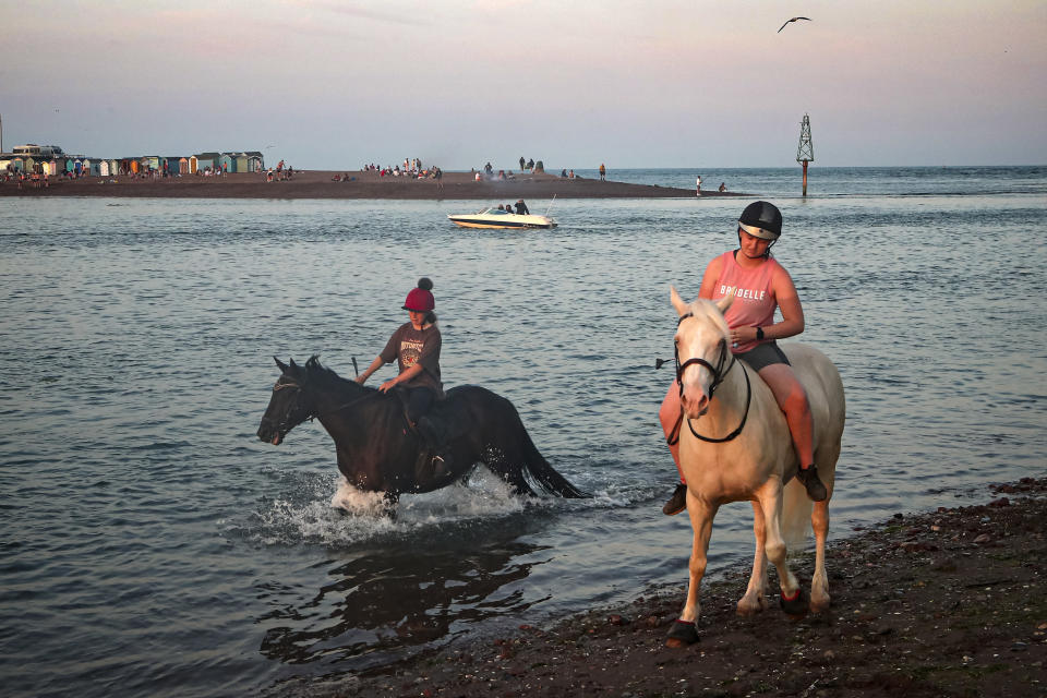 Riders take their horses into the sea at Shaldon, Devon, England, Thursday July 22, 2021. Visiting the fishing village of Shaldon a small cluster of mainly Georgian houses and shops at the mouth of the River Teign, is like stepping back into a bygone era. It features simple pleasures that hark back to analog, unplugged summer days: a book and a picnic blanket, a bucket and spade, fish and chips. (AP Photo/Tony Hicks)