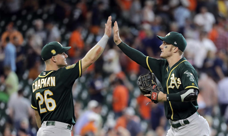 Oakland Athletics' Matt Chapman (26) and Mark Canha celebrate after a baseball game against the Houston Astros Thursday, July 12, 2018, in Houston. The Athletics won 6-4. (AP Photo/David J. Phillip)