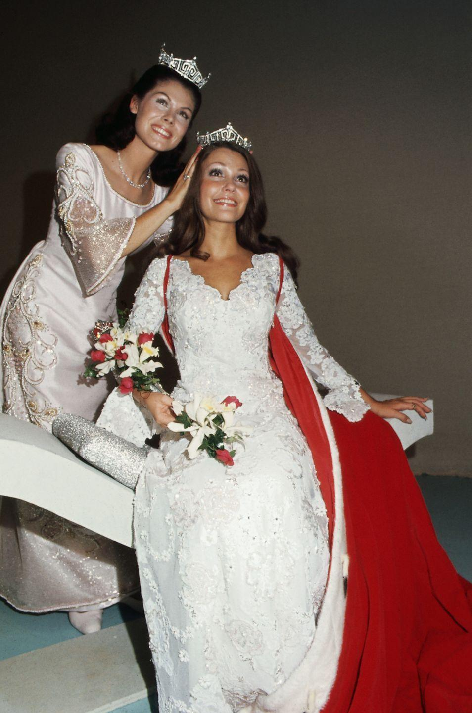<p>Terry Meeuwsen from Wisconsin, pictured here being crowned, opted for a lace bell-sleeve dress for her evening gown. The flowing design perfectly embodied the style of the '70s. </p>