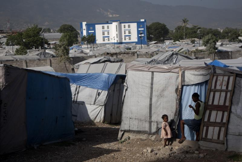 """In this Wednesday, June 13, 2012 photo, a woman and her daughter stand at the entrance of their tent in a camp for people displaced by the 2010 earthquake in Port-au-Prince, Haiti. Amid the horrors of Haiti's 2010 earthquake lay a promise of renewal. With the United States taking the lead, international donors pledged billions of dollars to help it """"build back better,"""" breaking its cycle of dependency. Yet 2 1/2 years later, the fruits of an ambitious $1.8 billion U.S. reconstruction promise are hard to find. (AP Photo/Dieu Nalio Chery)"""