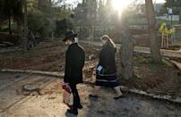 An ultra-Orthodox man and woman walk in a public park in Jerusalem; meetings between potential spouses must offer enough privacy for a personal conversation but be fully in public view