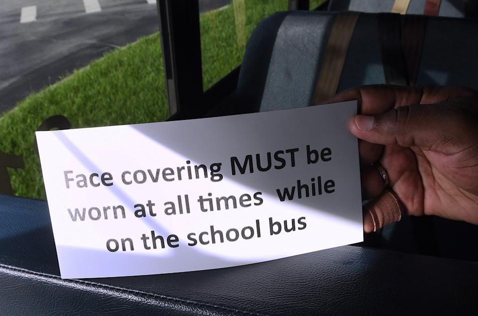 A sign about required masks is displayed on a school bus parked at the Winter Springs Transportation Hub of Seminole County Public Schools on Aug. 13 in Winter Springs, Fla. Not all districts are requiring students to wear masks, though, adding to drivers' anxieties. (Photo: Paul Hennessy/NurPhoto via Getty Images)