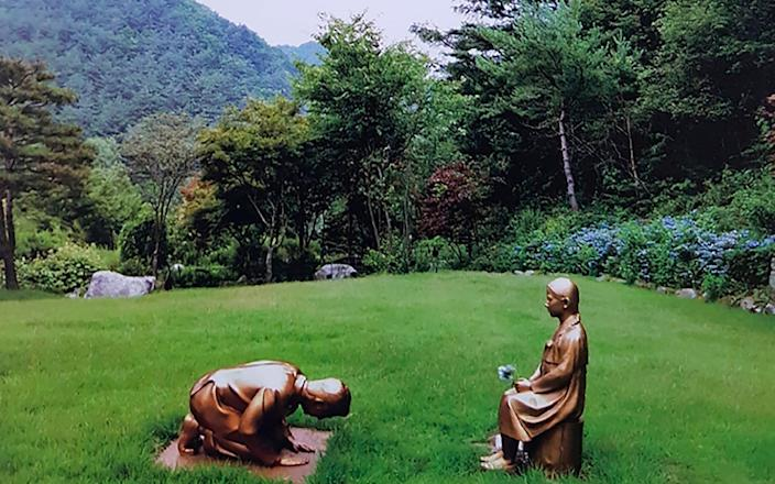The statue shows a man with a likeness to Shinzo Abe kneeling before a girl symbolising victims of sexual abuse by the Japanese during WWII - The Korea Botanical Garden/ The Korea Botanical Garden