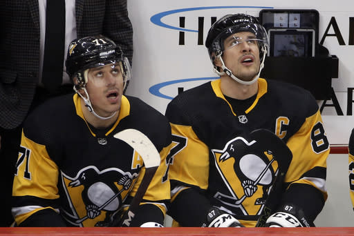 FILE - Pittsburgh Penguins' Evgeni Malkin (71) and Sidney Crosby (87) watch a replay of a goal by Malkin during the first period of the team's NHL hockey game against the Minnesota Wild in Pittsburgh, in this Jan. 14, 2020, file photo. The faces around Sidney Crosby and Evgeni Malkin change. The expectations around the Pittsburgh Penguins and their two longtime stars do not. After an offseason of retooling the coaching staff and tweaking the roster, the Penguins are hoping to rebound following a second straight early playoff exit. (AP Photo/Gene J. Puskar/File)