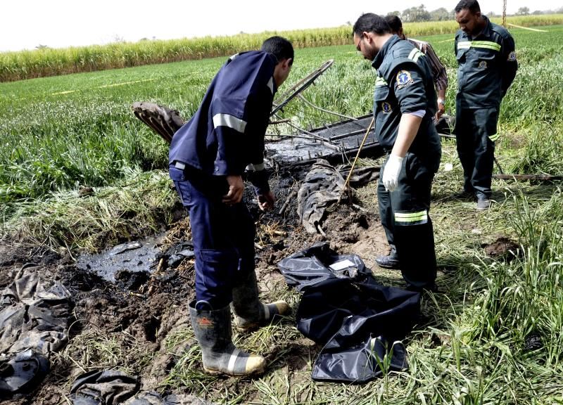 Egyptian rescue workers collect remains at the scene of a balloon crash outside al-Dhabaa village, just west of the city of Luxor, 510 kilometers (320 miles) south of Cairo, Egypt, Tuesday, Feb. 26, 2013. A hot air balloon flying over Egypt's ancient city of Luxor caught fire and crashed into a sugar cane field on Tuesday, killing at least 18 foreign tourists, a security official said. (AP Photo/Ibrahim Zayed)