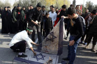 """Protesters burn representations of Israeli flag during a demonstration over the U.S. airstrike in Iraq that killed Iranian Revolutionary Guard Gen. Qassem Soleimani, in Tehran, Iran, Jan. 3, 2020. Iran has vowed """"harsh retaliation"""" for the U.S. airstrike near Baghdad's airport that killed Tehran's top general and the architect of its interventions across the Middle East, as tensions soared in the wake of the targeted killing. (AP Photo/Vahid Salemi)"""