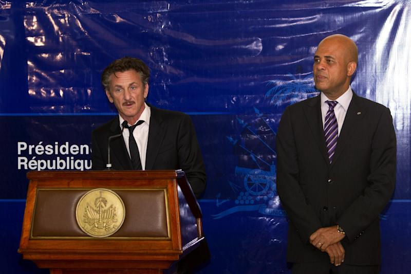 FILE - In this Tuesday, Jan. 31, 2012 file photo, U.S. actor Sean Penn, left, delivers a speech during a special ceremony at the national palace in Port-au-Prince, Haiti, accompanied by President Michel Martelly. Penn was been named ambassador at large for Haiti in recognition of his humanitarian work since the 2010 earthquake. The actor who stormed onto the scene of one of the worst natural disasters in history two years ago has certainly not lost interest. Defying skeptics, he has put down roots in Haiti, a country he hadn't even visited before the January 2010 earthquake, and has become a major figure in the effort to rebuild. (AP Photo/Ramon Espinosa)