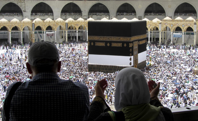 Muslim pilgrims pray as they watch thousands of pilgrims circumambulate around the Kaaba, the cubic building at the Grand Mosque, ahead of the Hajj pilgrimage in the Muslim holy city of Mecca, Saudi Arabia, Friday, Aug. 9, 2019. Hundreds of thousands of Muslims have arrived in the kingdom to participate in the annual hajj pilgrimage, a ritual required of all able-bodied Muslims at least once in their life. (AP Photo/Amr Nabil)