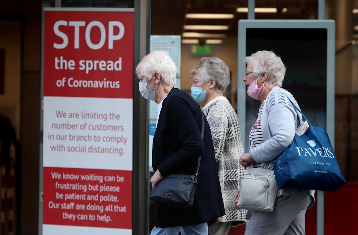 Members of the public wearing face masks walk passed a sign in a bank window in Glasgow. (Photo by Andrew Milligan/PA Images via Getty Images)