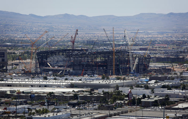 FILE - In this June 4, 2019, file photo, construction cranes surround a football stadium under construction in Las Vegas. The most compelling dramas in the NFL this season unfolded on the field, not off of it. And any thought that the league was in jeopardy of losing its spot as America's favorite sport has been set on the back burner. (AP Photo/John Locher, File)
