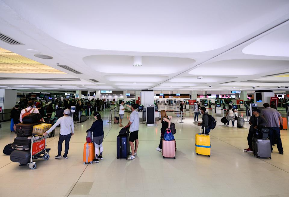 Travellers adhere to social-distancing rules as they check in for their flights at the Sydney International Airport.