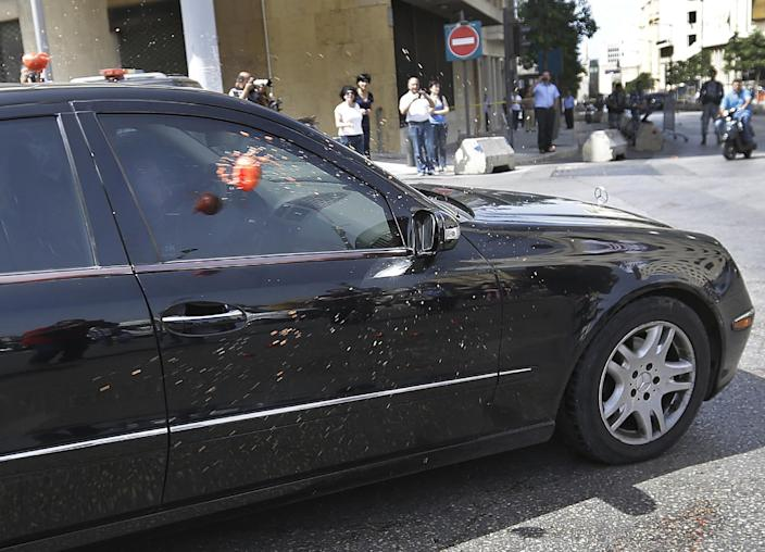 FILE - In this May 31, 2013, file photo, Lebanese lawmaker Imad al-Hout, who represents the Islamic group, is seen through his car window as it is pelted with tomatoes by pro-democracy protesters during a protest against the 17-month extending of the Lebanese parliament, in Beirut, Lebanon. Since the current parliament was elected in June 2009, the lawmakers have met 21 times to pass 169 laws, mostly related to raise government and civil servants' salaries, receive foreign aid and amend election law that will enable their re-election. In 2013, Lebanon's lawmakers only met twice to pass two laws, one of which was to extended their mandate for 18 months. (AP Photo/Hussein Malla, File)