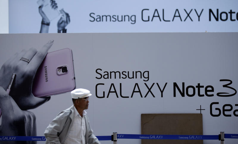 A South Korean man walks by an advertisement of Samsung Electronics' Galaxy Note 3 smartphone at a train station in Seoul, South Korea, Friday, Oct. 25, 2013. Samsung Electronics Co. had another record-high quarterly profit, thanks to revived semiconductor business and a record profit from handset sales. (AP Photo/Lee Jin-man)