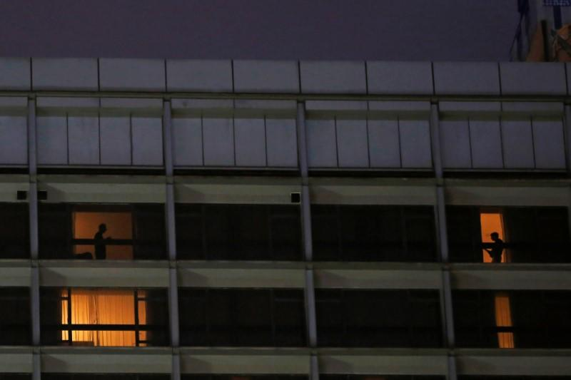 Guests are seen through the windows of a hotel, following the coronavirus disease (COVID-19) outbreak, in Hong Kong